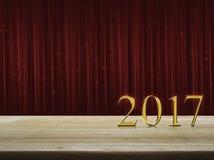 Texto 2017 del metal del oro de la Feliz Año Nuevo en la tabla sobre la cortina roja Imagenes de archivo