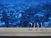 Texto 2017 del metal plateado de la Feliz Año Nuevo en la tabla de madera sobre ciudad Fotografía de archivo