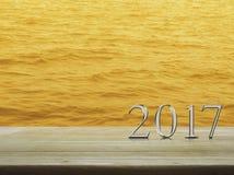 Texto 2017 del metal plateado de la Feliz Año Nuevo en la tabla de madera sobre el mar Fotos de archivo