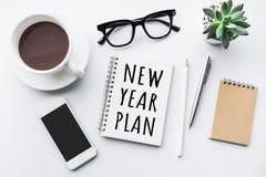 Texto del plan del Año Nuevo en la libreta con los accesorios de la oficina Imagen de archivo