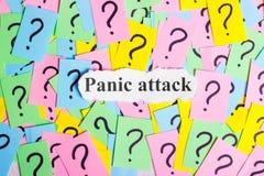 Texto del síndrome del ataque de pánico en notas pegajosas coloridas contra la perspectiva de signos de interrogación Fotografía de archivo