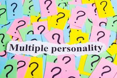 Texto del síndrome de la personalidad múltiple en notas pegajosas coloridas contra la perspectiva de signos de interrogación Fotografía de archivo