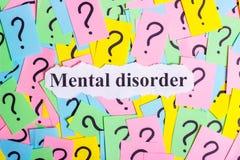 Texto del síndrome del trastorno mental en notas pegajosas coloridas contra la perspectiva de signos de interrogación Foto de archivo libre de regalías