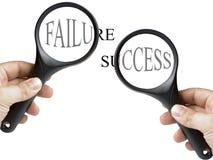 Texto del éxito y del fracaso debajo de la lupa Imagenes de archivo