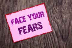 Texto do anúncio da escrita que mostra a cara seus medos Bravura corajoso da confiança conceptual de Fourage do medo do desafio d fotos de stock
