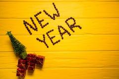 Texto do ano novo do café no fundo de madeira amarelo da prancha Fundo do ano novo Imagem de Stock Royalty Free