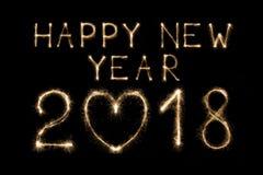 Texto do ano novo feliz 2018 feito da luz do fogo de artifício dos chuveirinhos isolada no fundo preto Foto de Stock