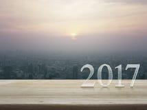 Texto do ano novo feliz 2017 na tabela de madeira sobre a cidade do por do sol Fotografia de Stock Royalty Free