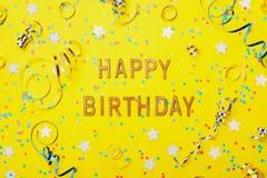 Texto do cumprimento do feliz aniversario decorado com confetes e serpentina na opinião superior do fundo amarelo estilo liso da  fotos de stock royalty free