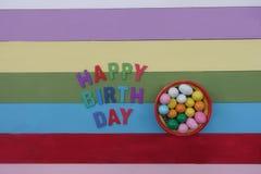 Texto do feliz aniversario com multi letras e chocolates de madeira coloridos imagens de stock royalty free