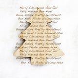 Texto do Feliz Natal em uns três de madeira Fotografia de Stock Royalty Free