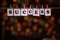 Texto do sucesso em papéis com os pregadores de roupa com bokeh da festão no fundo Fotografia de Stock Royalty Free