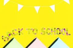 Texto dos botões da cor de volta à escola no fundo amarelo com papel colorido, lápis pretos, festão das bandeiras brancas imagem de stock