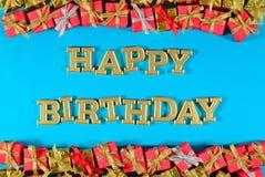 Texto dourado do feliz aniversario e presentes dourados e vermelhos em um azul Fotografia de Stock