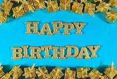 Texto dourado do feliz aniversario e presentes dourados em um azul imagem de stock