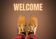 Texto e sapatas bem-vindos de Brown nos pés com fundo marrom Foto de Stock Royalty Free