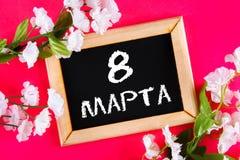 Texto en ruso: 8 de marzo Pizarra negra y flores blancas Día internacional del ` s de las mujeres Imágenes de archivo libres de regalías