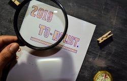 Texto 2019 escrito à mão da lista de afazeres no papel com marcador, compasso e lupa do uso imagem de stock