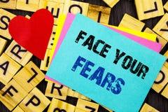 Texto escrito à mão que mostra a cara seus medos Bravura corajoso da confiança conceptual de Fourage do medo do desafio da foto e imagem de stock