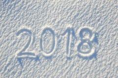 texto 2018 escrito en la nieve para la textura o el fondo - concepto de las vacaciones de invierno Día soleado, luz brillante con Foto de archivo libre de regalías