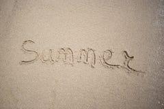 Texto feito à mão na areia em um verão da inscrição da praia - Sun e mar Imagem de Stock Royalty Free