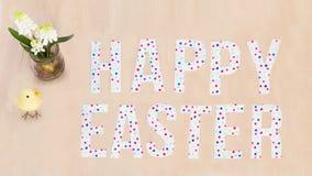 Texto feliz colorido brilhante da Páscoa, pintainho, flores no backgr de madeira Imagens de Stock Royalty Free