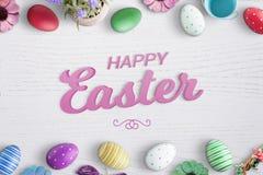 Texto feliz de easter 3D na mesa de madeira branca cercada com os ovos e as flores coloridos de easter Foto de Stock Royalty Free