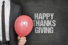 Texto feliz de la acción de gracias de Holding Balloon With del hombre de negocios en la pizarra Imagen de archivo