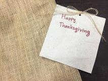 Texto feliz de la acción de gracias en el papel marrón y harpillera en la etiqueta de madera imagen de archivo libre de regalías