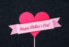 Texto feliz del día del ` s de la madre en una cinta alrededor de un corazón Foto de archivo
