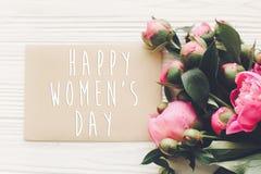 Texto feliz do dia do ` s das mulheres no cartão e ramalhete cor-de-rosa das peônias no rusti Fotos de Stock Royalty Free