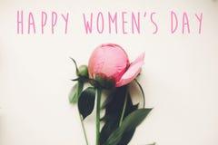 Texto feliz do dia do ` s das mulheres no ramalhete cor-de-rosa das peônias no branco rústico w Fotos de Stock