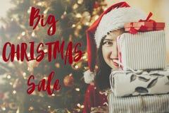 Texto grande de la venta de la Navidad Oferta del descuento del día de fiesta Muchacha feliz en s fotos de archivo
