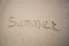 Texto hecho a mano en arena en un verano de la inscripción de la playa - Sun y mar Imagen de archivo libre de regalías