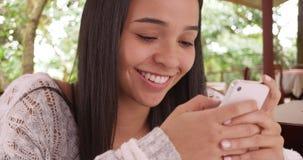 Texto hispánico joven del teléfono celular de la lectura de la muchacha en restaurante Fotografía de archivo libre de regalías