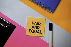 Texto justo e igual em notas pegajosas com conceito da mesa de escritório da cor fotografia de stock