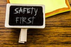 Texto manuscrito que muestra el concepto del negocio de la seguridad primero para la advertencia segura escrita en tablero del av Imagen de archivo