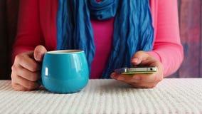 Texto que mecanografía de la mujer en el teléfono y té de consumición, comunicación y conexión metrajes