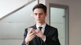 Texto que mecanografía del hombre de negocios en smartphone en oficina metrajes