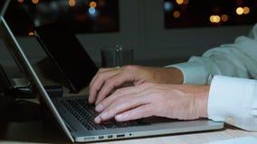 Texto que mecanografía del hombre de negocios o codificación en el teclado del ordenador portátil con las manos por la tarde, pri almacen de metraje de vídeo
