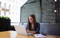 Texto que mecanografía del redactor de anuncios acertado de la mujer joven en el red-libro portátil durante resto en restaurante Imagen de archivo