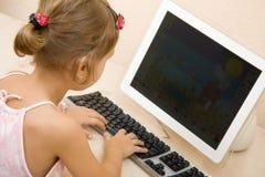 Texto que pulsa de la niña en el ordenador Imágenes de archivo libres de regalías