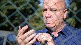 Texto sério do homem usando um telefone celular atrás de uma cerca metálica video estoque