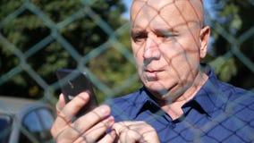 Texto sério do homem usando um telefone celular protegido por uma cerca metálica filme