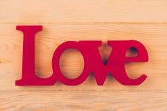 Texto vermelho do amor na tabela de madeira Imagem de Stock Royalty Free