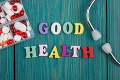 Texto y x22; Buen Health& x22; de letras, del estetoscopio y de píldoras de madera coloreados Imágenes de archivo libres de regalías