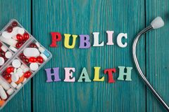 Texto y x22; Health& público x22; de letras, del estetoscopio y de píldoras de madera coloreados Imagenes de archivo