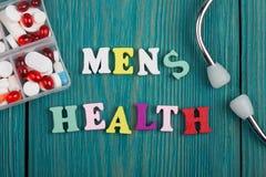 Texto y x22; Men& x27; health& x22 de s; de letras, del estetoscopio y de píldoras de madera coloreados Fotografía de archivo