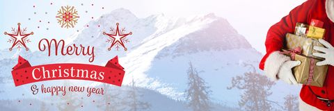 Texto y Papá Noel de la Feliz Año Nuevo de la Feliz Navidad con los regalos Imagenes de archivo
