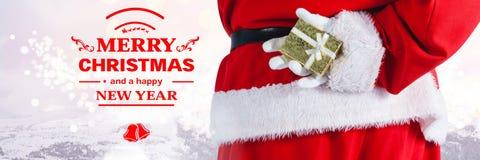 Texto y Papá Noel del Año Nuevo de la Feliz Navidad con el regalo Imagen de archivo libre de regalías